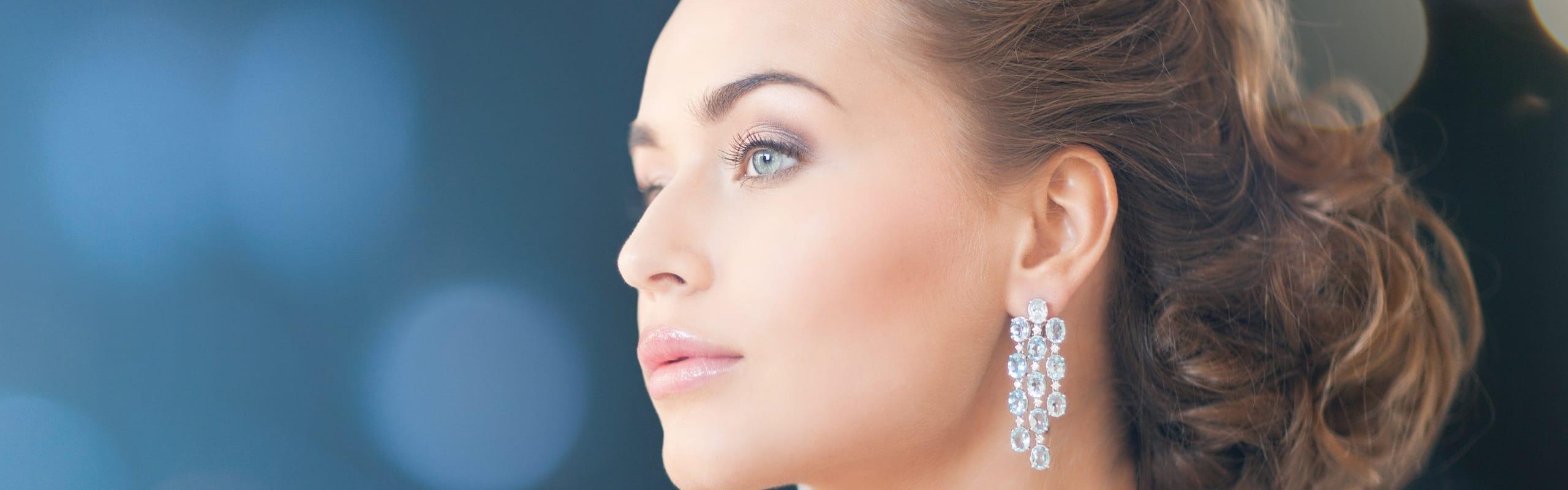 Dame mit funkelnden Ohrringen und strahlender Haut durch Anti-Aging Behandlung